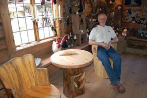 Provsitter. Bernt Blomgren tar en paus i en av sina kubbstolar. Två av dem är gjorda av björkar som stod vid Leksands kyrka. Foto:Linnea Kallberg