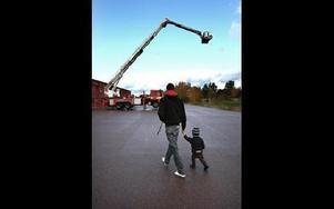 Felix Stjernlöf, 2, med pappa Daniel tar bestämda steg mot en av de större brandbilarna.