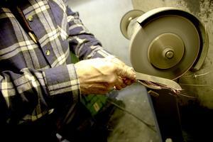 På slipmaskinen, med stor precision, slipar Stig till eggen på slaktkniven.