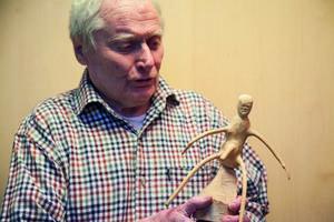 Träkonstnären Evert Eriksson visar upp en av sina fräcka figurer.