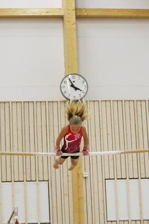 En gymnast från Stockholm känner på barren som är en av de grenar deltagarna tävlar i under helgen.