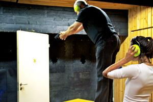 Försedd med hörselkåpor får konstnären Linda Shamma Östrand hjälp av Lars Melin hos Söderhamnspolisen att skjuta 17 kulor genom dörren som sedan ska ingå i installationen.