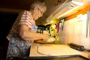 Bre på smör. Hjördis Gustafsson brer på smöret på två tredjedelar av degen hon nyss kavlat ut. Sen strör hon på kanel och socker.
