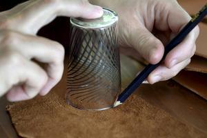 Monica Karlstein har limmat fast läderdekorationer på ett färdigt kuddfodral. Hon använde ett litet glas för att markera en lång rad halvcirklar och klippte sedan remsor som var vågiga nedtill och raka upptill. Remsorna limmades sedan på fodralet nedifrån och upp.