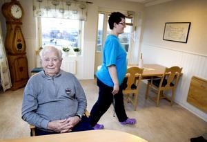 Stig Hillman har bott i tre år hos Carema Care i Stigslund och trivs bra. I bakgrunden syns vårdbiträdet                                              Jessica Larsson.