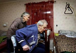 Med mycken möda lyckas Inge Sjölander ta sig från rullstolen till sängen med hjälp av hustrun Helga. Men något avlastningsboende får han inte, trots att också Helga börjar få en del krämpor.