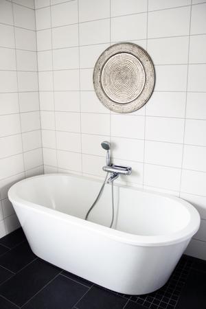 Över badkaret har Therese placerat överdelen till ett brickbord som dekoration.