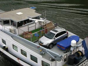 På flodpråmen finns ibland hela skepparfamiljen med. Bilen lyfts i land med en kran och barnens lekhage har höga staket för att förhindra att någon trillar över bord.