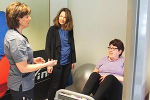 Sjukgymnasten Liselotte Skoglund-Eriksson berättar för landstingsrådet Malin Gabrielsson (KD) om artros-skolan. Margaretha Sikhammar kämpar i benpressen.