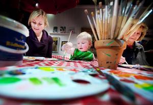 """Inne på Jamtlis målarkafé så sitter tre generationers tjejer och framställer framtida mästerverk – mamma Catrin Hedström, dottern Saga Hedström och mormor Ingrid Eriksson. Lilla Saga Hedström tog det lite försiktigt i början med målandet. Men sedan upptäckte hon silverfärgen och att man kan droppa färg. """"Det regnar"""", säger hon.Foto: Håkan Luthman"""