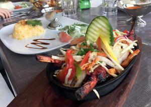 Välkryddade, rykande heta lammracks täckta med grönsaker serveras direkt i en oval gjutjärnspanna vid bordet.