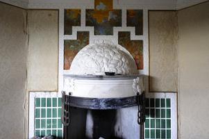 Spiskåpan är smyckad med lövverk. Ovanför skildras ett italienskt landskap, men den öppna spisen ser ut som en soptipp. Foto:Kjell Jansson