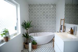 Badrummet på entréplanet har renoverats med mönstrat golv som får sträcka ut sig på ena väggen.
