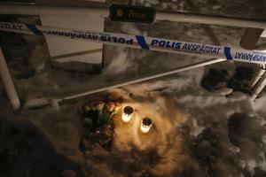 Tända ljus och blommor utanför det hus där en 22-årig kvinna knivdödades i Mölndal.