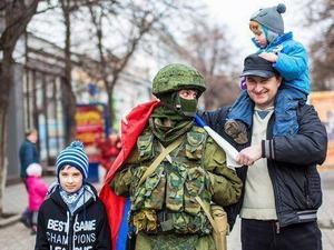 Invånarna välkomnar de ryska soldaterna med rosor i staden Kerch på Krim-halvön.