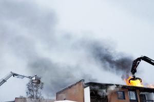 Taket lyfts bort för att brandmännen ska komma åt brandhärdarna.