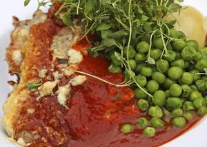 Bildtext 7: Långlagrad ost och tomat är säkra umamikällor. Piccata, det vill säga ostpanerad kalvschnitzel med tomatsås och sockrade ärtor, är en stor smakupplevelse, i synnerhet om osten är långlagrad.    Foto: Dan Strandqvist