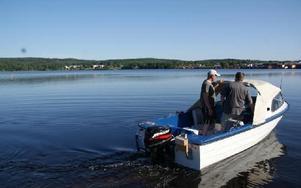 Motorbåten på väg ut för att släppa ålarna i Ljusterns vatten.