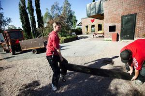 Stefan Gelinder och Daniel Byström på väg med det nya konstverket - bronsplankan. Nu ska fundamenten grävas så att plankan kan läggas som en sittplats i Folkets hus nya trädgård.