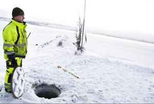 Berth Andersson väntar på att kollegan Stefan Lundin ska komma upp ur dagvattenbrunnen med ett vattenprov som ska analyseras.