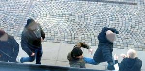 Flera av de demonstrerande männen börjar slå och sparka en förbipasserande man.