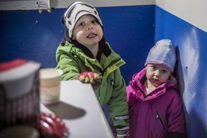 Saft och kex finns att köpa för barn inne i den lilla stugan. På bild, Dante 4,5 år och Stina Höös 2,5 år, från Herrö. Pappa Jacob Lindberg håller ett öga på barnen när de leker medan mamma, Sara Höös, kör några varv runt isbanan.