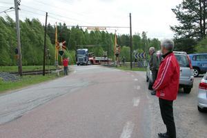 Vägombuden från Motormännen tittar på hur en långtradare lastad med långa rör tar sig igenom kurvan vid järnvägsövergången i Ramsjö. Lastbilar måste gå över på andra sidan för att klara kurvan.