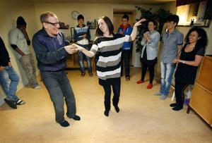Abbe visar hur en bugg går till. Madeleine Persson är vägledare på Härkes asylboende. Hon planerar att ta hela gänget på dans i påsk. Efter några kvällar med Abbe är de redo.