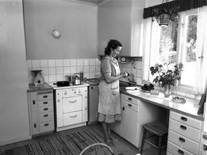 Ett ljust och modernt kök. Praktiskt diskbänk, elspis, lampa ovanför och dagsljus.