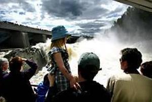 Foto: GUN WIGH Vattenföreställning. Nina Back från Älvkarleby är trygg hos pappa Heine när hon kollar in det första vattenpåsläppet i älven. Men det skummande vattenmolnet når ändå hennes ansikte.