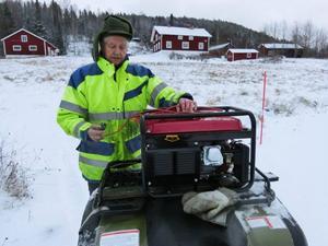 John Westerlund i Börjesjö kör fyrhjuling i strömlöst land, på väg med reservaggregat till en granne.