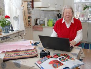 Dock-Dagny hemma vid köksbordet, där dockorna fått lämna plats för en kamera, en dator och vid det här tillfället också Dagnys bok om bygdens påsömmerskor.