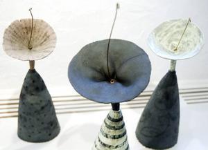 Bibbi Forsmans keramikblommor i vas blir som små lyssnande paraboler ut mot världen och rummet.