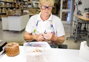 Susanne Olsson är anställd sedan tio år tillbaka och här klipper hon vackra band som används till paketeringen.