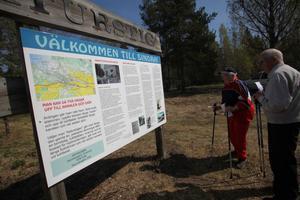 Karin Wallin och Nils Karlsson uppskattar informationsskylten som kommit på plats vid Sindra kraftverk.