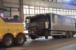 Lastbilen bärgas bort efter att den dragits ut från Åhléns på Drottninggatan i Stockholm.