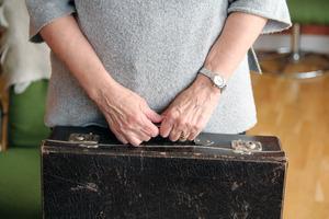 Juliette Lundin med sin resväska i brun papp där alla hennes ägodelar låg när hon reste till Sverige 1946.