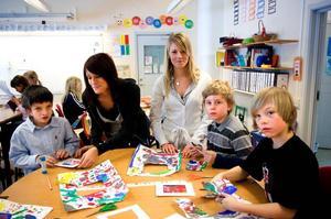 Välgörande. Caroline Fällman och Karin Svensson lär barn att hjälpa andra barn i sitt projektarbete på gymnasiet. På torsdagen styrde de över tillverkningen av ramar på de tavlor barnen målat.