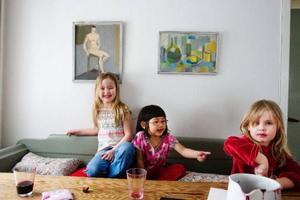 Elvy och Tora Nyberg, 8 respektive 4 år gamla, trivs under farmor Birgit Ståhl-Nybergs tidiga tavlor i kökssoffan i Håxås tillsammans med grannen Helle Björnsdotter, 5.