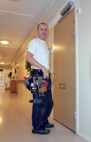 Joakim Hallin sätter upp dörrstängare på alla dörrar. Vid ett brandlarm stängs dörrarna automatiskt.