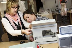 Textillärare Britt-Marie Eklund hjälper Linda Söderlind med maskininställningarna.