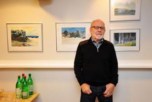 Konstnären Olle Christoffersson bland sina akvareller från Gotland som visas på biblioteket.