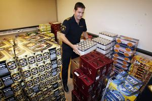 Kommissarie Tommy Gustavsson bland den beslagtagna alkoholen.