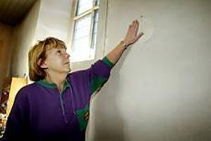Foto: LASSE WIGERTStulna. Berit Engström, kyrkvaktmästare, drar handen över den tomma väggen där mässingslampetterna hängde.