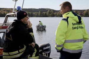 Brandmannen Anders Karlsson och Göran Pålsson, driftchef vid Seab, diskuterar bilbärgningen.