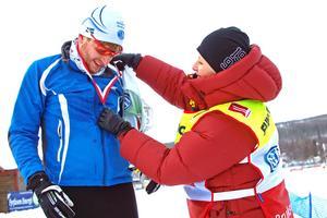 Johan Nilsson från Göteborgs skidklubb får en medalj av funktionären Katarina Ahltin.