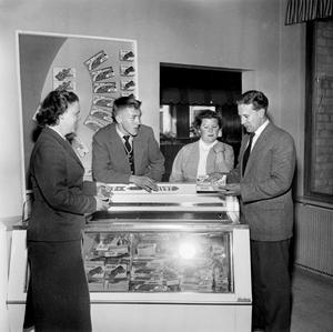 Frionor torsk går det att läsa på affischen bakom herrarna och damerna. Djupfryst mat var en nyhet på 50-talet.