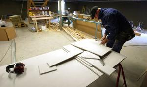 Joakim Persson skär gipsskivor som ska användas till väggarna.
