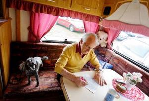 Karl-Johan Skogman i sin egen lilla bingolokal. Han var först på plats med husvagn, något som många andra tagit efter. Dvärgpudeln Pyret engagerar sig också i husses bestyr.