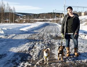 Jennie Berggren med sina två hundar Nemo och Otis, nedanför järnvägsstationen i Timrå som hon menar skulle passa utmärkt att anlägga en hundpark på.